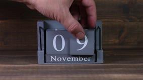 устанавливая дата 09 на деревянном календаре куба на месяцы в ноябре акции видеоматериалы