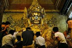 Устанавливать листовое золото на статуе золота Будды в виске Mahamuni в Мандалае Стоковая Фотография