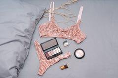 Установите блестящего стильного сексуального женского белья шнурка с аксессуарами женщины на серой предпосылке простынь Покупки и стоковое изображение
