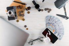 Установите для перемещения на белой предпосылке: деньги, камера, трутень, телефон и другие аксессуары плоско кладут стоковая фотография rf