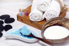 Установите для процедур по курорта от кокосового масла, мягких полотенец, горячих камней и голубой соли для принятия ванны на бел Стоковые Изображения RF
