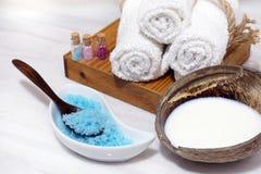 Установите для процедур по курорта от кокосового масла, мягких полотенец, и голубой соли для принятия ванны на белой мраморной та Стоковая Фотография