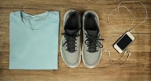 Установите для спорт: ботинки, футболка, мобильный телефон с концом-вверх на деревянной предпосылке, взгляд сверху наушников Стоковое Фото