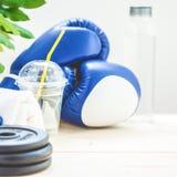 Установите для спорт, полотенца, перчаток бокса, гантели и бутылки воды на светлой предпосылке Концепция здорового образа жизни C Стоковое фото RF