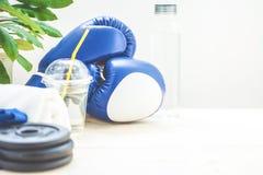 Установите для спорт, полотенца, перчаток бокса, гантели и бутылки воды на светлой предпосылке концепция здорового образа жизни п Стоковые Фото