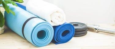 Установите для спорт, циновки йоги, полотенца, гантели и бутылки воды на светлой предпосылке Концепция здорового образа жизни Стоковые Изображения RF