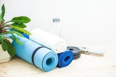 Установите для спорт, циновки йоги, полотенца, гантели и бутылки воды на светлой предпосылке Концепция здорового образа жизни Co Стоковая Фотография RF