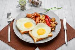 Установите для яичниц завтрака, зажаренных овощей, сосисок Хлеб на деревянной таблице стоковые изображения rf