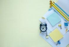 Установите канцелярских принадлежностей школы назад в школа: карандаши, часы, блокнот, правитель на желтой предпосылке образовани стоковые изображения