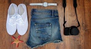 Установите одежды для идти к морю: джинсы замыкают накоротко, тапки, вахты, photocamera, раковины, взгляд сверху деревянной предп Стоковое Фото
