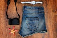 Установите одежды для идти к морю: шорты джинсов, вахты, photocamera, раковины, взгляд сверху деревянной предпосылки Стоковое фото RF