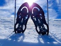 установите пары snowshoes или ракеток снега и 2 поляков лыжи на холодном белом снеге готовом для того чтобы идти на снежную гору  стоковые фото