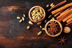 Установите специй анисовки звезды, кардамона, циннамона и желтого сахарного песка на старой деревянной предпосылке стоковая фотография rf