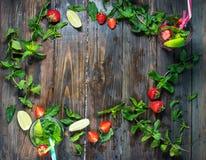 Установите с коктеилями известки и клубники mojito на деревянной предпосылке Стоковое Изображение