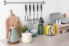 Установите чистых cookware, блюд, утварей и приборов на таблице на стене стоковое фото rf