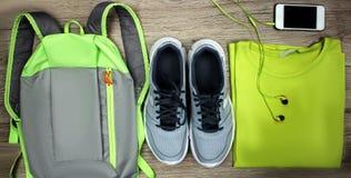 Установите для ботинок спорт, рюкзака, футболки, мобильного телефона с концом-вверх на деревянной предпосылке, взгляд сверху науш Стоковое фото RF