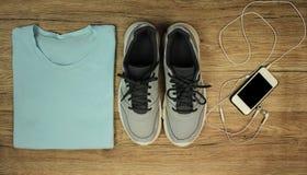 Установите для спорт: ботинки, футболка, мобильный телефон с концом-вверх на деревянной предпосылке, взгляд сверху наушников Стоковая Фотография