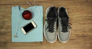 Установите для спорт: ботинки, футболка, мобильный телефон с наушниками и красный конец-вверх на деревянной предпосылке, взгляд с Стоковое фото RF