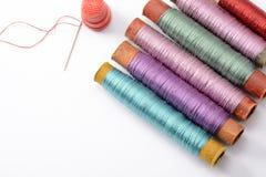 Установите для шить, пестротканые катушек с потоками, иглы и кольца на белой предпосылке Стоковая Фотография