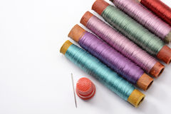 Установите для шить, пестротканые катушек с потоками, иглы и кольца на белой предпосылке Стоковые Фотографии RF