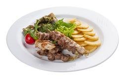 Установите kebabs с гарниром овоща на белой плите стоковое фото