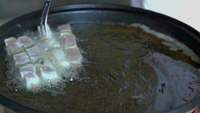 Установка зажаренных кубов мяса на протыкальники в масло видеоматериал