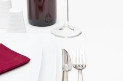 Установка места с белыми плитами и красным вином Стоковые Фотографии RF