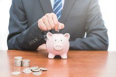 Установка монеток в piggy концепцию банка- сбережений стоковая фотография rf