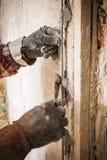 Установка направляющих маяков металла для заполнять и выравнивать стен в ремонте Рука покрывает стену с гипсолитом стоковая фотография rf