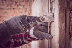 Установка направляющих маяков металла для заполнять и выравнивать стен в ремонте Рука покрывает стену с гипсолитом стоковое изображение