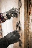 Установка направляющих маяков металла для заполнять и выравнивать стен в ремонте Рука покрывает стену с гипсолитом стоковые изображения