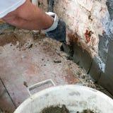 Установка направляющих маяков металла для заполнять и выравнивать стен в ремонте Рука покрывает стену с гипсолитом стоковые фото