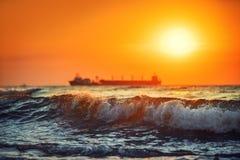 Установка на море с грузовим кораблем плавания, сценарный взгляд Солнця стоковые изображения