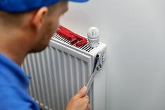 Установка системы отопления и ремонтное служба водопроводчик устанавливая радиатор стоковая фотография