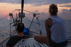 Установка Солнця в океан с взглядом от парусника с женщиной и человеком в Гондурасе, Центральной Америке стоковое фото