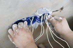 Установка стенной розетки Работа на устанавливать электрические выходы Электрик подготавливает выходы проводки подходящие стоковые фото