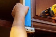 Установка шарниров мебели на мастере двери шкафа сверлит дверь шкафа Стоковая Фотография