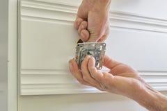Установка электрических гнезд в древесине, крупном плане руки электрика устанавливая пролом в стене в доску панели стены деревянн стоковая фотография rf