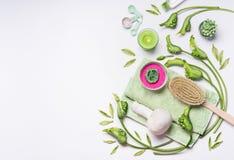 Установка PA с зелеными цветками и заводами, инструментами массажа, солью моря, полотенцем и свечой на белой предпосылке, взгляд  стоковое изображение