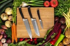 Установленные кухонные ножи на деревянной разделочной доске с предпосылкой свежих овощей : стоковые изображения rf