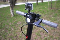 Установлено колесо скутера, камера действия Электрическая чернота скутера с серыми ручками стоковые фото