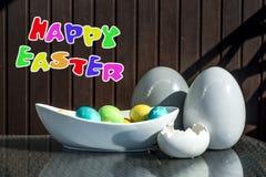 Установленные красочные сияющие пасхальные яйца и серый цвет и белизна покрасили керамический с текстом счастливой пасхой Стоковые Фото