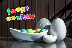 Установленные красочные сияющие пасхальные яйца и серый цвет и белизна покрасили керамический с текстом счастливой пасхой в немце Стоковые Изображения RF