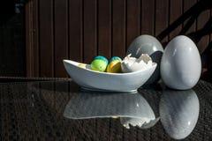 Установленные красочные сияющие пасхальные яйца и серый цвет и белизна покрасили керамический и отражение на таблице Стоковое Изображение RF