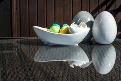 Установленные красочные сияющие пасхальные яйца и серый цвет и белизна покрасили керамический и отражение на таблице Стоковое Изображение