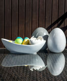 Установленные красочные сияющие пасхальные яйца и серый цвет и белизна покрасили керамический и отражение на таблице Стоковая Фотография RF