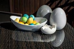 Установленные красочные сияющие пасхальные яйца и серый цвет и белизна покрасили керамический и отражение на таблице Стоковые Фотографии RF