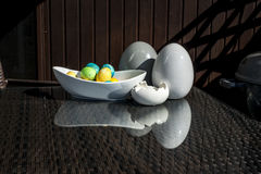 Установленные красочные сияющие пасхальные яйца и серый цвет и белизна покрасили керамический и отражение на таблице Стоковое Фото