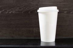Устранимая горячая кофейная чашка на таблице в кофейне стоковая фотография rf
