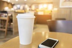 Устранимая горячая кофейная чашка с smartphone на деревянном столе в c стоковое фото rf